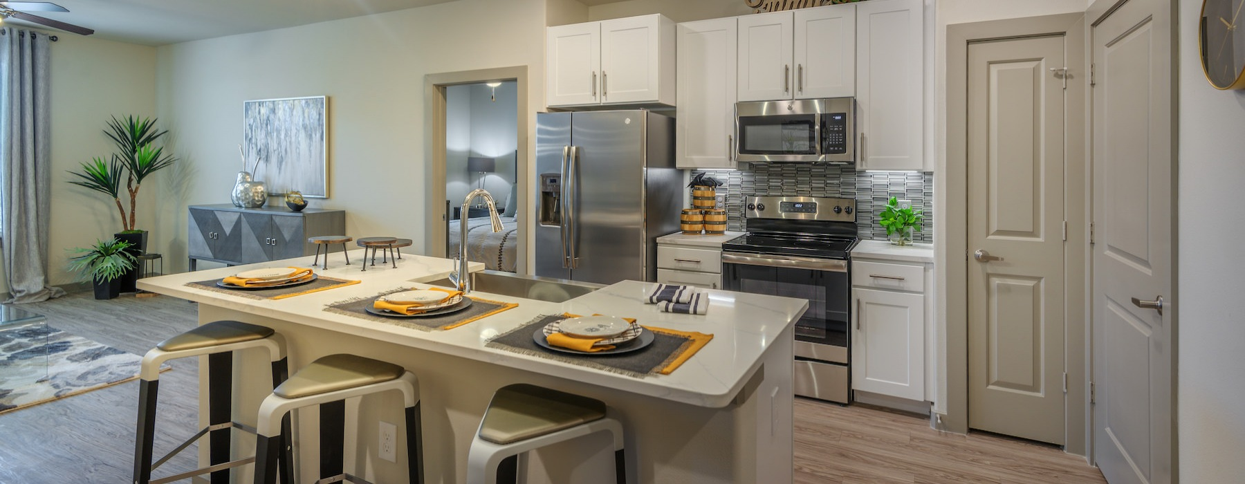 Model unit at Radius West showinng the ktichen and its island with an open door to the bedroom