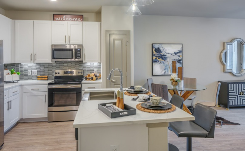 Model Unit at Radius West showing the kitchen with island and living room with wood floors