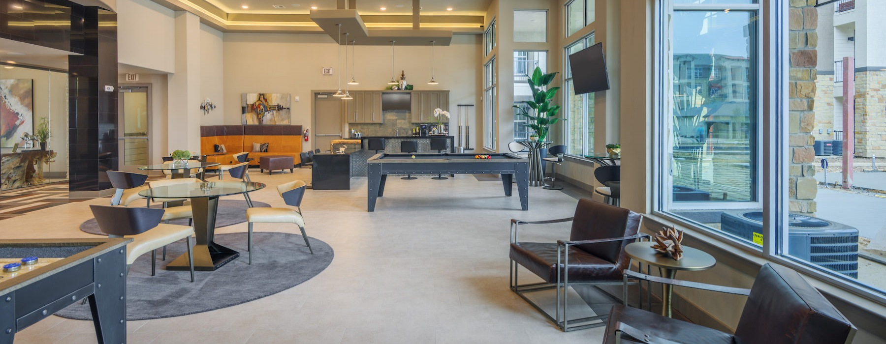 Model unit at Radius West showing the community room with tables, chairs, pool table, and food bar area
